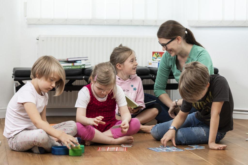 Vier Kinder sitzten zusammen mit der Familienberaterin Annika Peyk auf dem Boden und spielen und unterhalten sich mit ihr