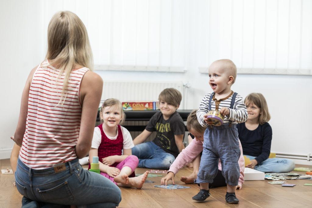 Vier Kinder sitzen auf dem Fußboden, ein kleiner Junge steht und alle schauen eine vor ihnen sitzende Erzieherin an und lächeln