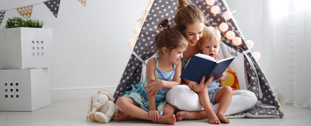 Mutter liest in einem gemütlichen Spielzelt zwei Kindern ein Buch vor