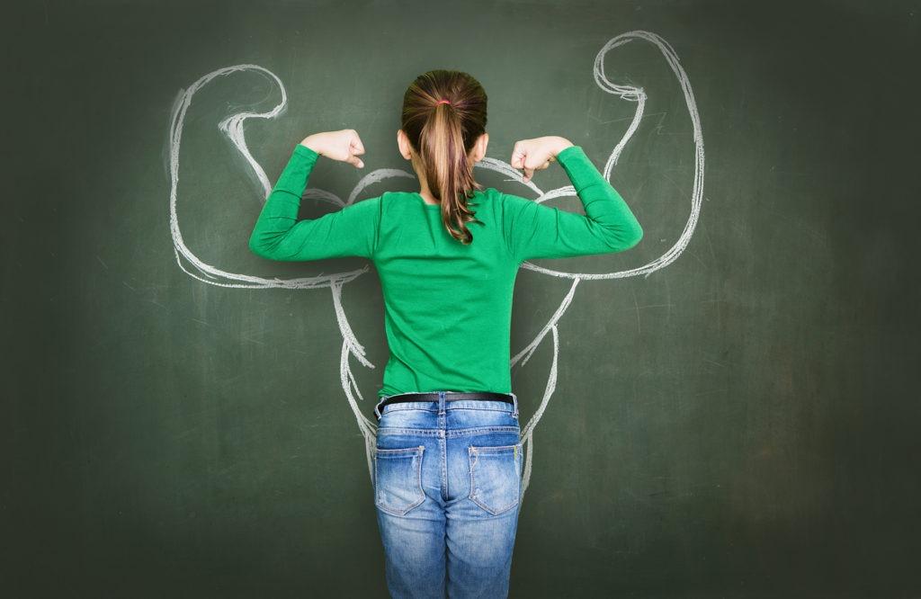 Mädchen von hinten, wie sie die Arme anspannt um ihre Muskeln zu zeigen. Sie steht vor einer Tafel, auf der ihre Silhouette mit großen Muskeln mit Kreide aufgemalt ist.