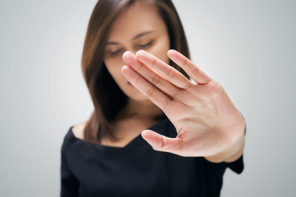 Eine Frau zeigt mit ihrer Hand ein klares, abwehrendes Nein
