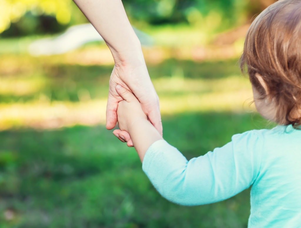Kleinkind hält die Hand ihrer Mutter beim Spazieren im Park