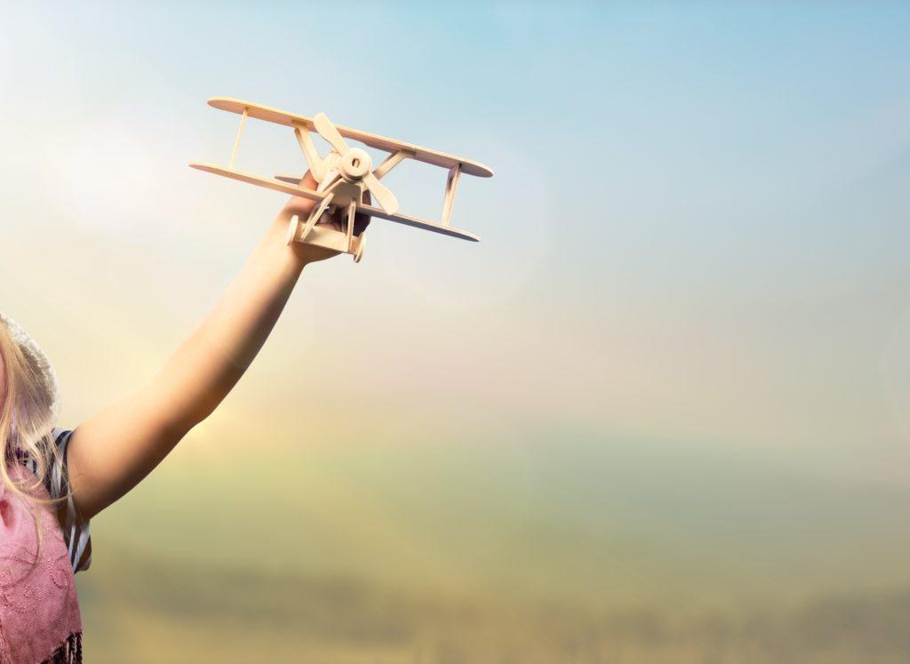 Kind spielt draußen fröhlich mit Holzflugzeug, es wirkt ausgelassen und glücklich